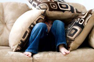 Het Gezinsleven - Moeder en kind - Kinderen 4-12 jaar - Kinderen met faalangst - Jongen verstopt onder de kussens van de bank