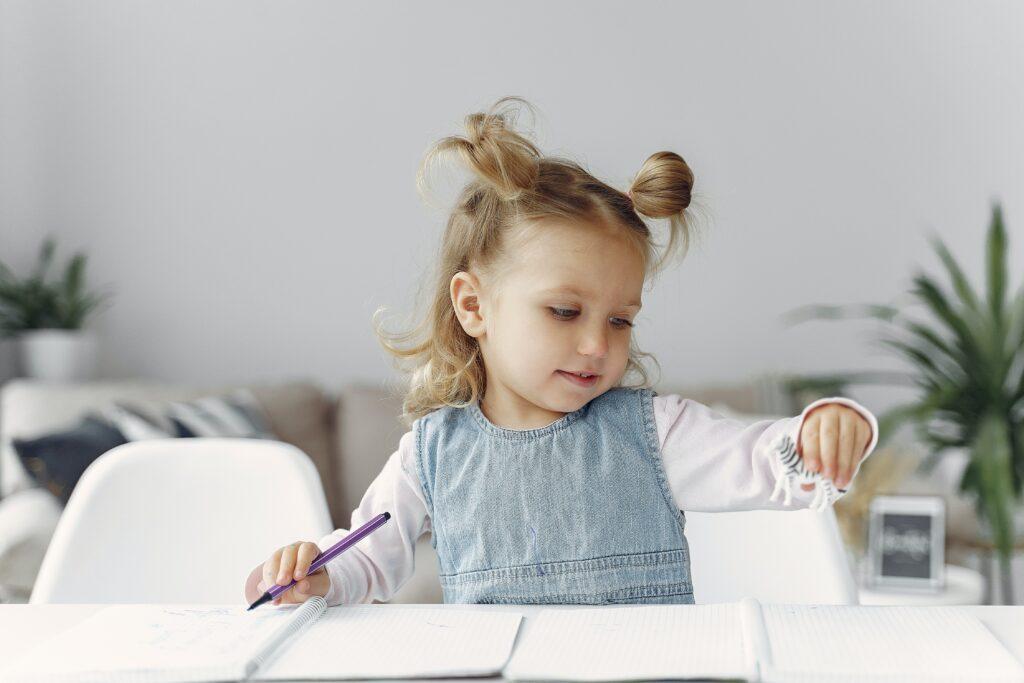 Het Gezinsleven - Moeder & kind - Kinderen 4-12 jaar - TOS, een onbekende taalontwikkelingstoornis - meisjes probeert een dierennaam te schrijven